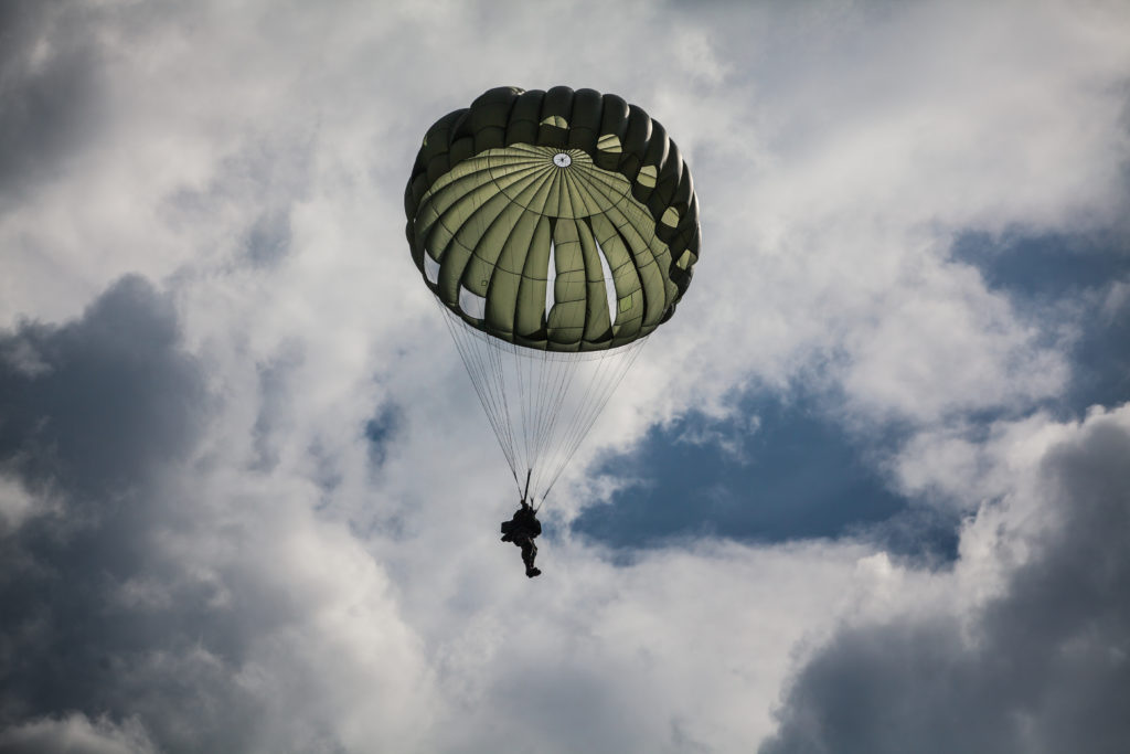 Military parachutist in the war cloudy sky